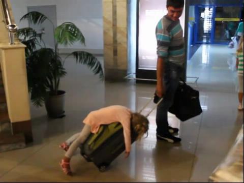 千奇百怪人间百态; 可爱小萝莉困得无法挪步 趴在粑粑行李箱上睡着了